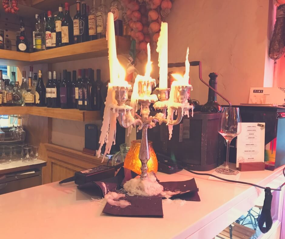 A candlestick with real candles sitting on a  bar.