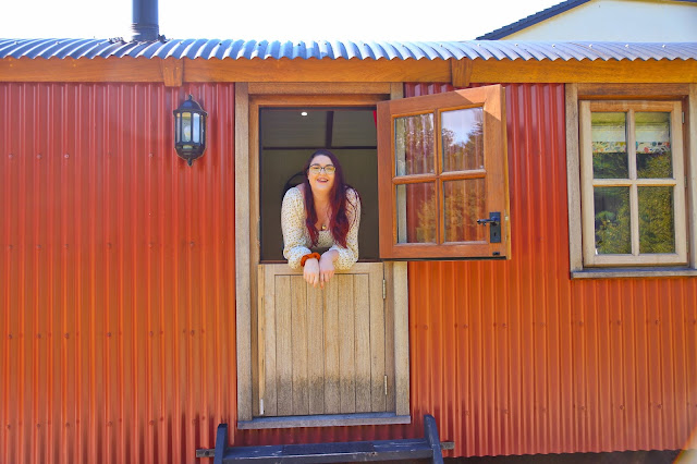 Becky leaning out of the door of a cabin in South Wales