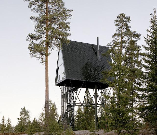 cabaña elevada sobre estructura negra en medio del bosque