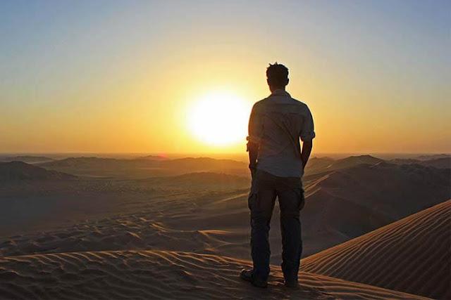 Hombre parado contemplando el atardecer y resignado a perder un amor
