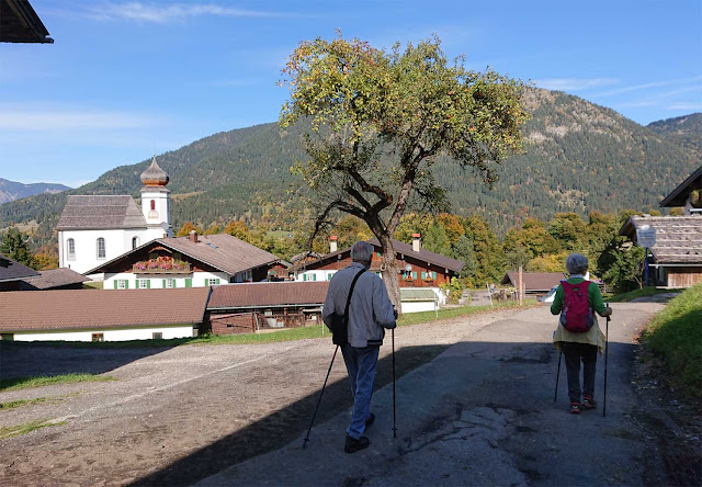Wanderer mit Stöcken im Kirchdorf Wamberg, St. Anna Kirche im Hintergrund