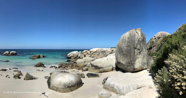 Big cloudless blue sky over the green-blue ocean and a white sand beach with large boulders.