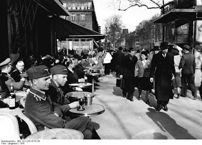 An outdoor cafe, small round tables facing a street with heavy foot traffic. Two uniformed German soldiers sit at the nearest, watching people pass. Black and white.