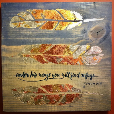 wooden plaque with foil feathers and handlettering of under his wings you will find refuge Psalm 91:4