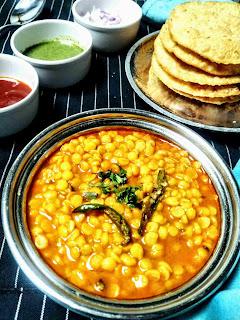 Serving dal pakwan in a bowl, some pakwan , green chutney imli chutney and onion chopped in background