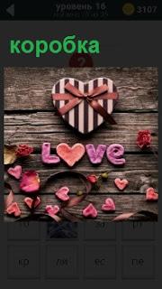 На деревянной поверхности лежит коробка в виде сердца с бантиком и выложено слово любовь