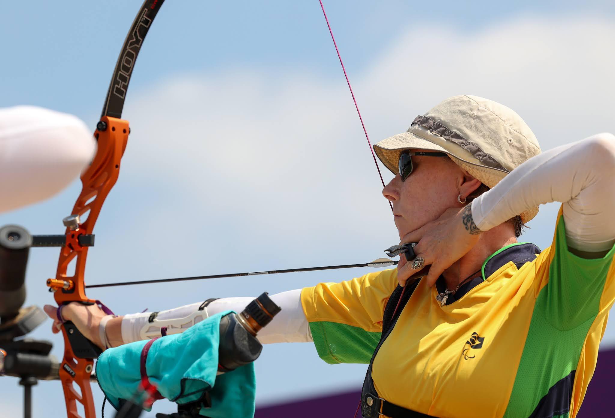 Fabíola Dergovics, de uniforme amarelo, chapéu e óculos, segura o arco e mira