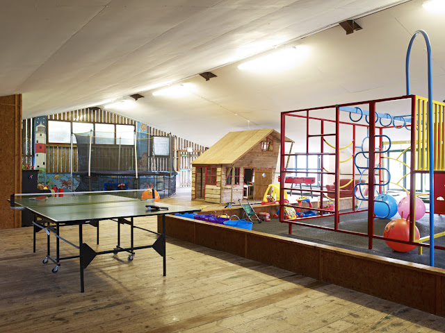 An indoor play area with trampoline, climbing frame, play house and other toys
