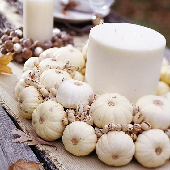 This candle centerpiece with mini white pumpkins and pistachios is unique.