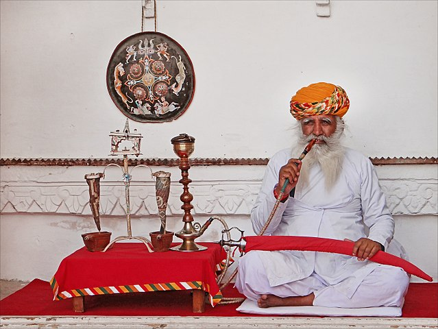 An old Rajasthani man smoking hukkah with sword in his hand