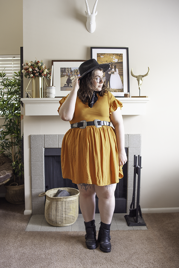 An outfit consisting of a black wide brim fedora, a black and white dotted neck scarf, a yellow short sleeve flounce dress, a black and silver double buckle belt and black chunky boots.