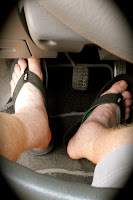 View of car pedals with driver in flip flop footwear