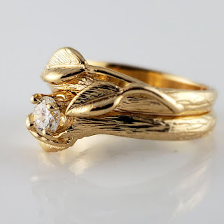 Hand sculpted branch style texture with three hand sculpted leaves cast in 14k yellow gold with a .25 natural diamond.
