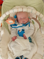 A baby sleeping in a gliding chair