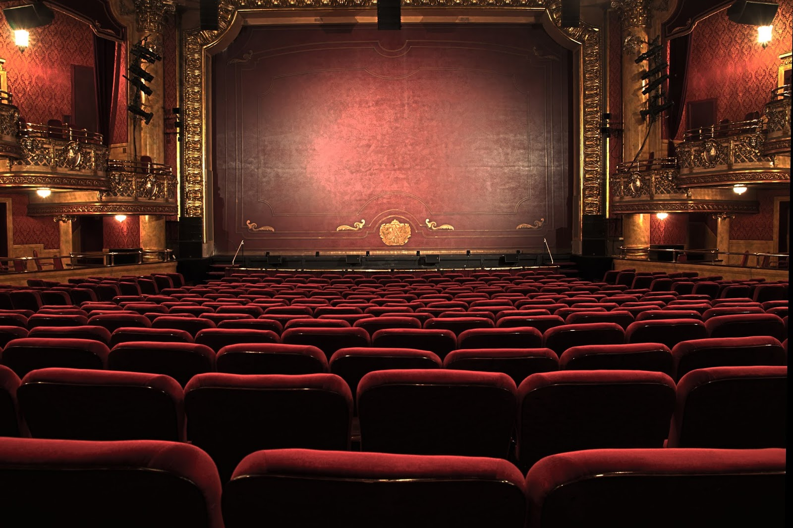 A photo inside a theatre, at the back of the stalls looking over the red seats towards the stage with it's red safetly curtain down