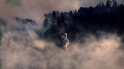 Astronauta en la tierra entre niebla por el bosque