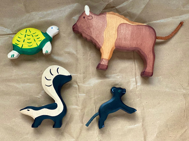 A selection of ethical carved animal toys including a tortoise, skunk small panther and bison