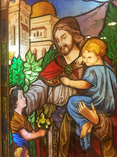 stained glass window depicting Jesus and children
