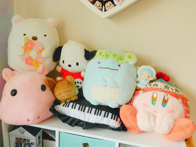 A photo showing a collection of plushies won playing the Japanese Ichiban Kuji game: a hippo, a dog, a polar bear, a nintendo character called Kirby, a little boy with blue hair, the pokemon eevee and a dinosaur