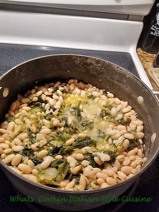 this is a stovetop sauce pot filled with cannellini beans and escarole
