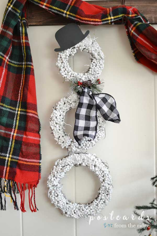 snowman wreath with buffalo check scarf and black paper hat
