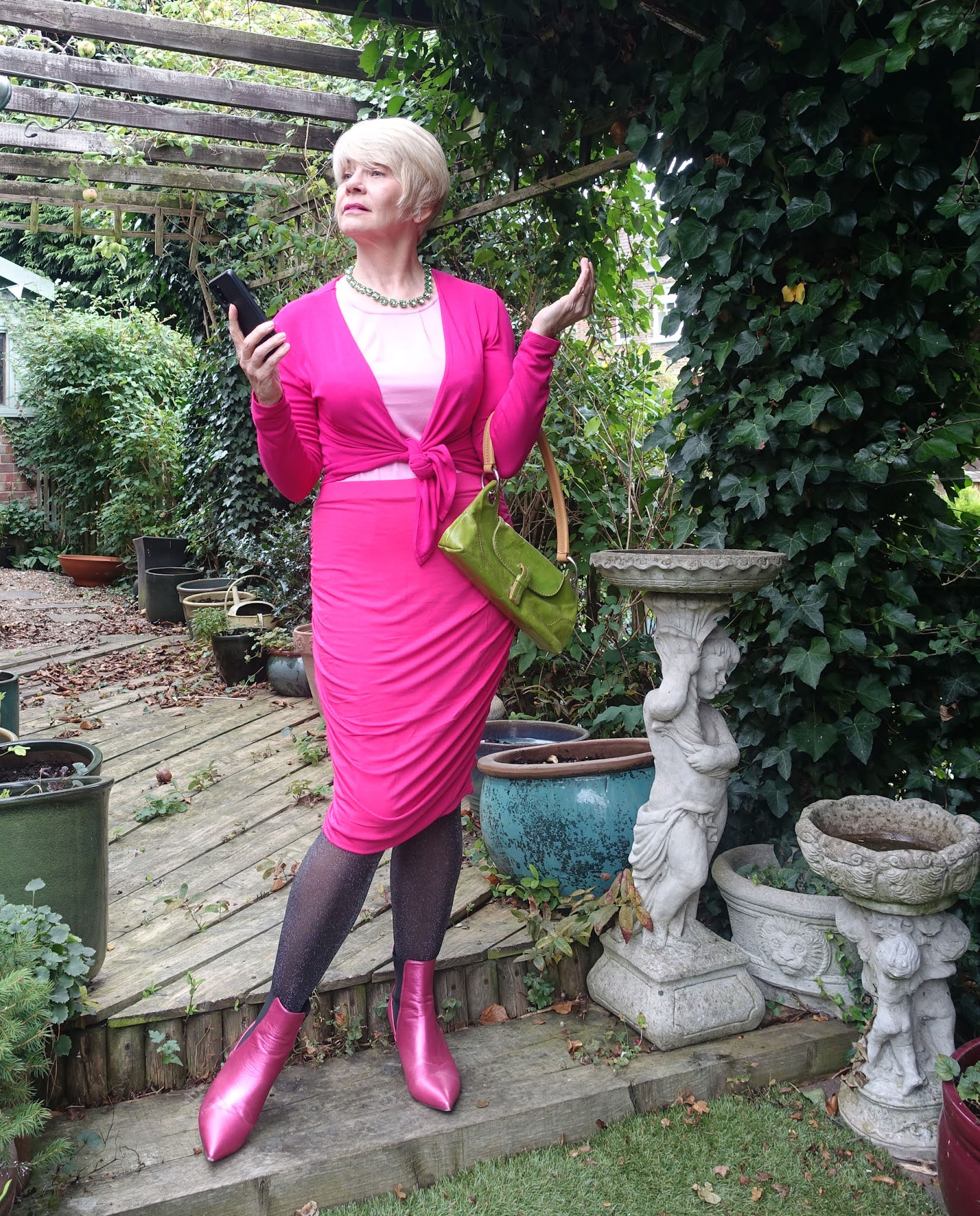 Striking a theatrical pose, Gail Hanlon from Is This Mutton in ruched skirt, short tie wrap and top in pink from Kettlewell and pink boots