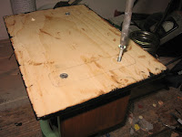 Attaching the base to the case with four 1 1/4 inch wood screws