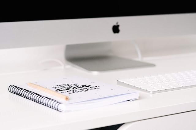 Agenda e Caneta sobre um Mesa com Computador Macbook e Teclado