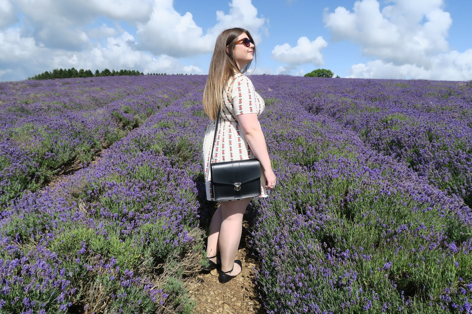 Grace is standing in a field of lavender. She is turned to the side and her black satchel can be seen hanging from her shoulder