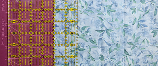 Quilting ruler on blue fabric with previously cut veritcal lines visible.