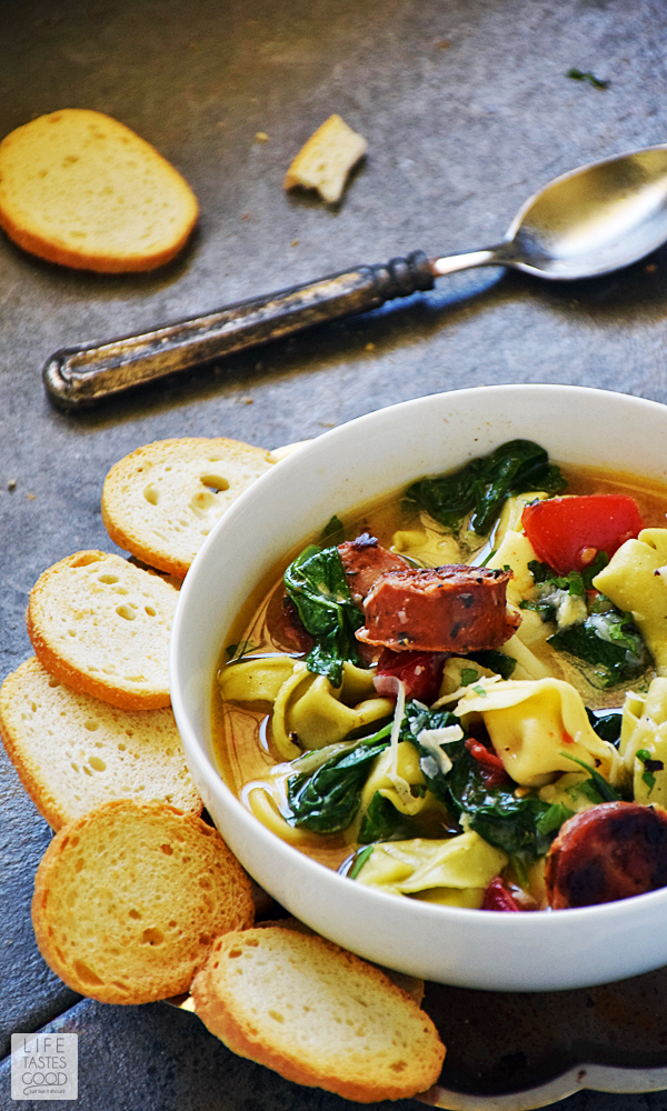 This Easy Tortellini Soup | by Life Tastes Good uses fresh ingredients to maximize flavor, but I also cheat using cooked sausage to save time. The soup makes a hearty and satisfying meal you can have on the table in 30 minutes from start to finish! #LTGrecipes