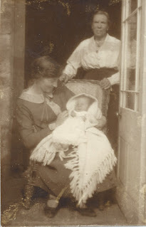 Mother seated wit baby, Grandmother behind chair