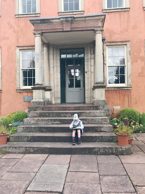 Little boy sitting on steps of a grand house
