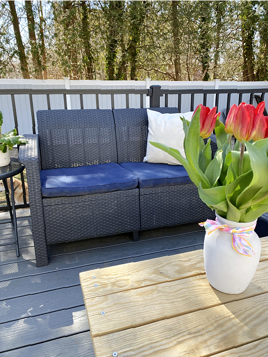 outdoor love seat with painted blue cushions and vase of tulips