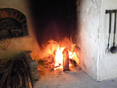 Large 18th-century cooking fireplace with wood fire burning. Beehive oven in wall and metal cooking utensils are also seen.
