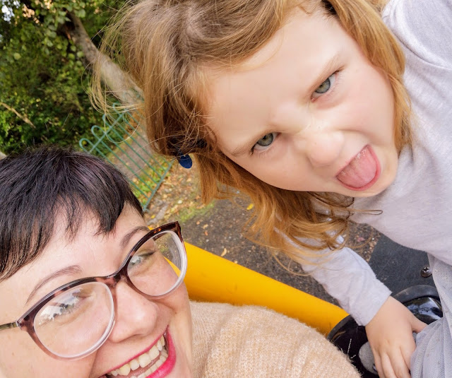 Image of a mother and daughter on a playground. The mother has a short pixie haircut and is wearing tortoise shell glasses and bright lipstick . She is smiling. The daughter has long blonde hair that is flowing over her shoulders. The girl is pulling a silly face and sticking out her tongue.