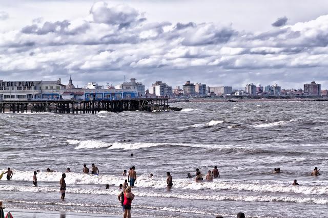 Gente en la playa con mar picado