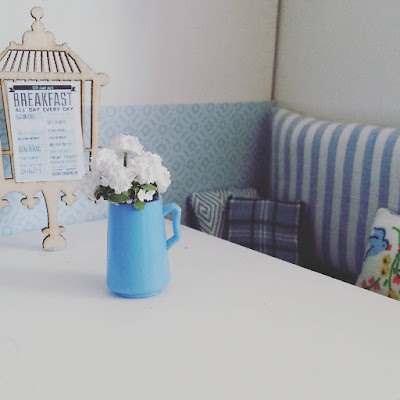 One-twelfth scale modern miniature cafe corner with a table, a menu in a bird-cage shaped holder, a jug of flowers and a bench seat with cushions.