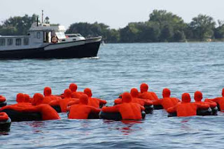 A Boat Approches Safety Orange Swimmers