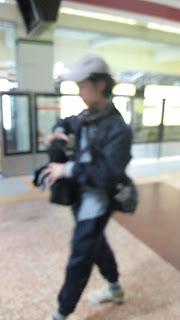 Zé andando na estação de trem. O ângulo da foto não está bem enquadrado na figura do garoto e o foco está borrado.