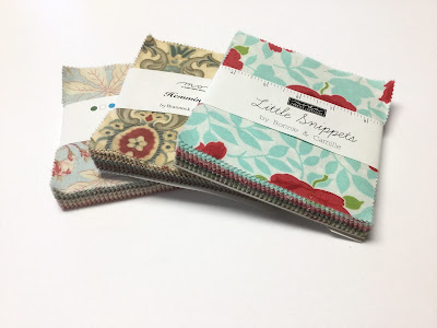 A collection of fabric Charm Packs containing five inch squares