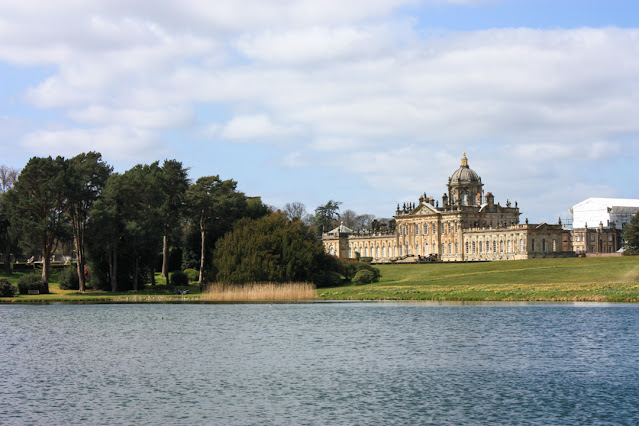 View across a small lake with Castle Howard in the distance.