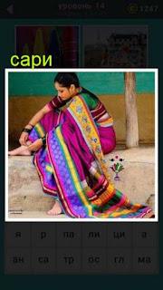 сидит женщина одетая в национальную одежду сари и вешает на ноги украшения
