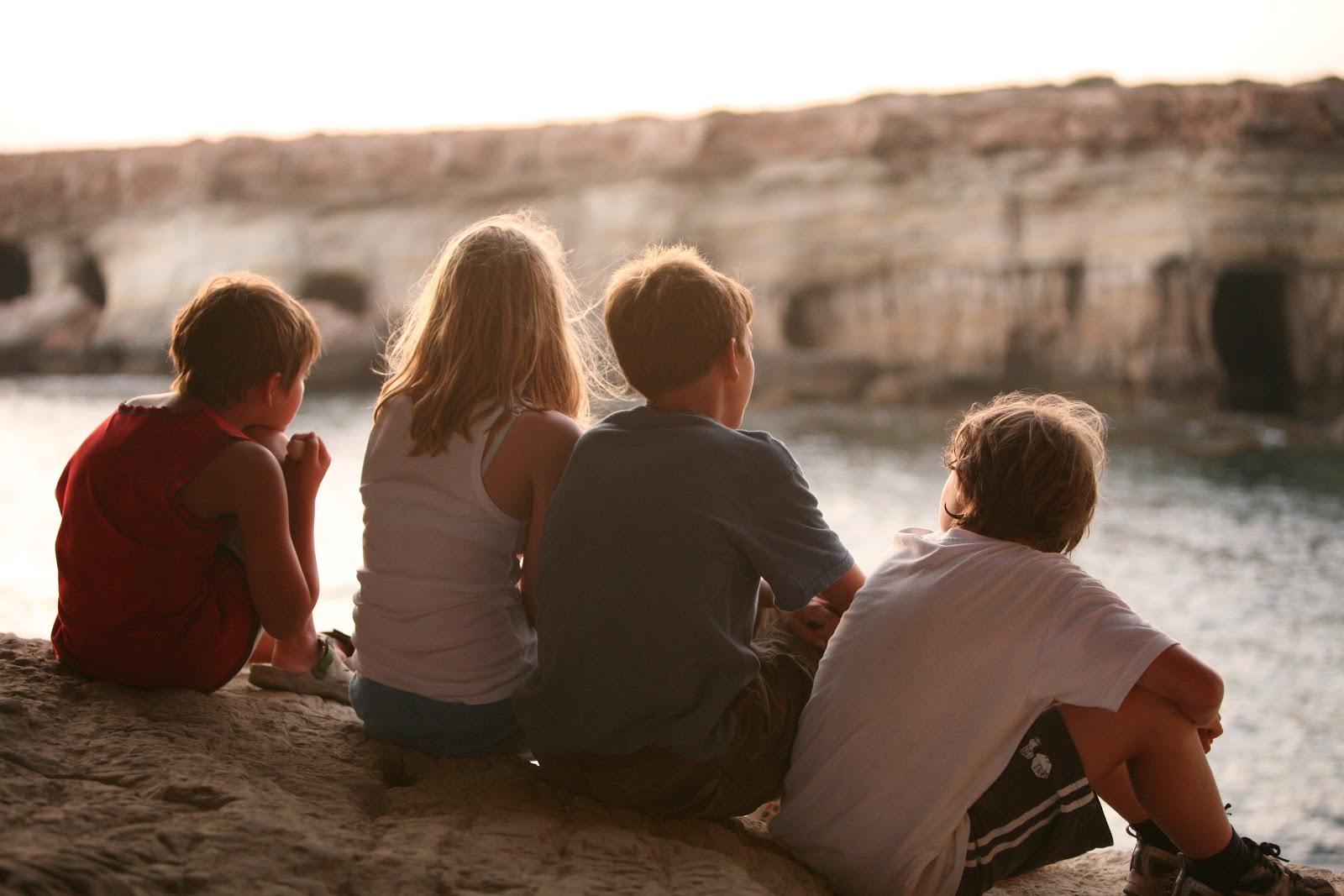 座っている四人の子供の友達同士の後ろ姿
