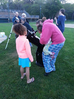 Image of The youngest attendee getting her first look at the Moon through a telescope