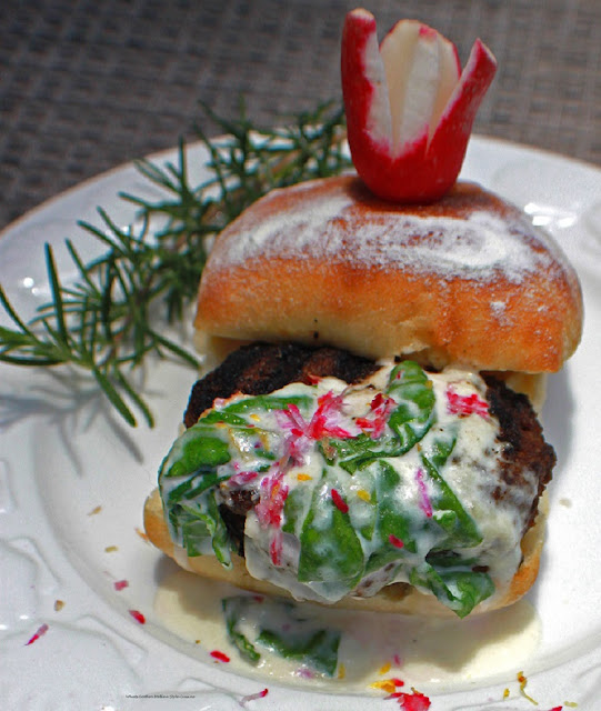 This is a hamburger on a white plate with spinach lemon cream sauce over the top with a sprig of rosemary on the plate on a ciabatta roll with a flowered radish on top recipe card