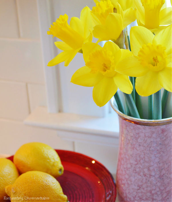Daffodils in a red vase with lemons on a red cake plate nearby