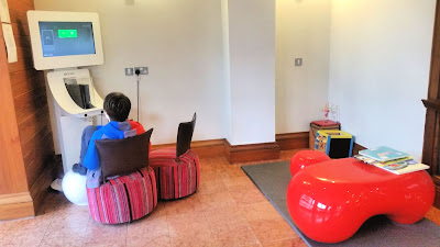 The children's games area, featuring an Xbox station, a box with toys and red table with books on.