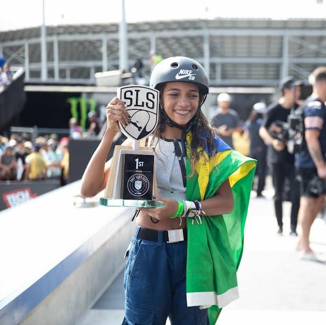 Rayssa Leal sorrindo com a bandeira do Brasil no seu braço direto e com o troféu de campeã da etapa sendo segurada com as duas mãos
