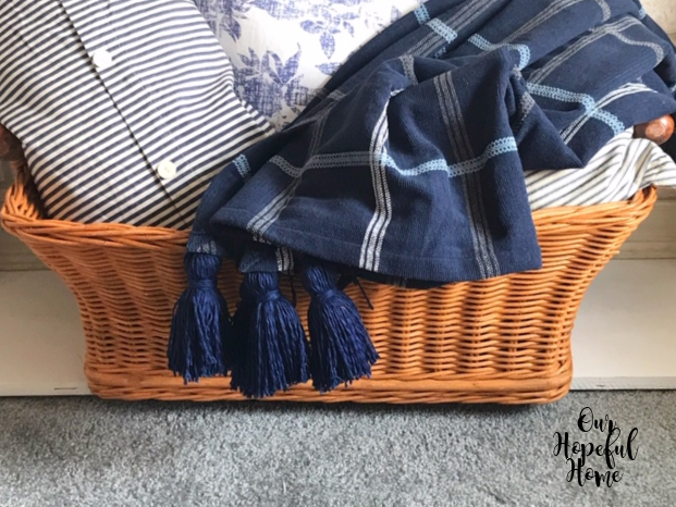 blue throw and blue pillows in basket